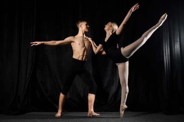 Joven pareja de ballet bailando y posando