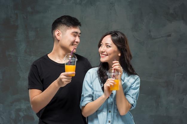Una joven pareja bastante asiática con unas copas de jugo de naranja