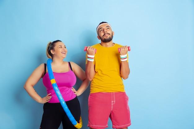 Joven pareja bastante caucásica en la formación de ropa brillante sobre fondo azul concepto de deporte, emociones humanas, expresión, estilo de vida saludable, relación, familia. practicando con aro y pesas.