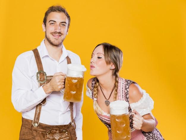 Joven pareja bávara con jarras de cerveza