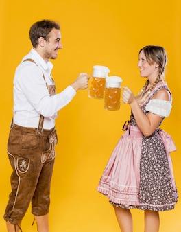 Joven pareja bávara tostado cervezas
