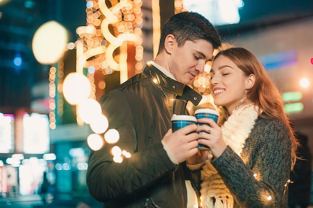 Joven pareja besándose y abrazándose al aire libre en la calle de noche en navidad