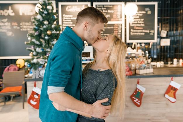 Joven pareja besándose cerca del árbol de navidad en la cafetería
