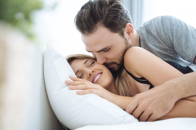 Joven pareja besándose la mejilla en la cama se despierta por la mañana.