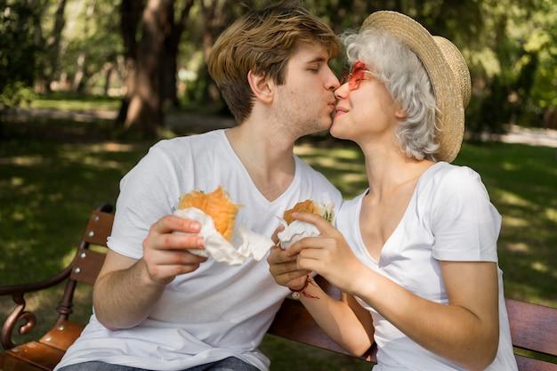 Joven pareja besándose mientras disfruta de hamburguesas en el parque