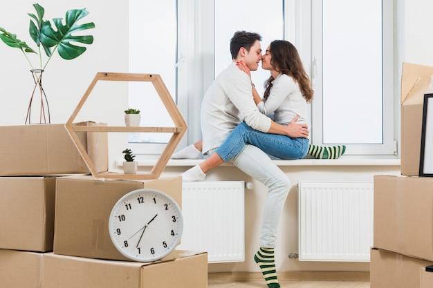Joven pareja besándose en su nuevo hogar