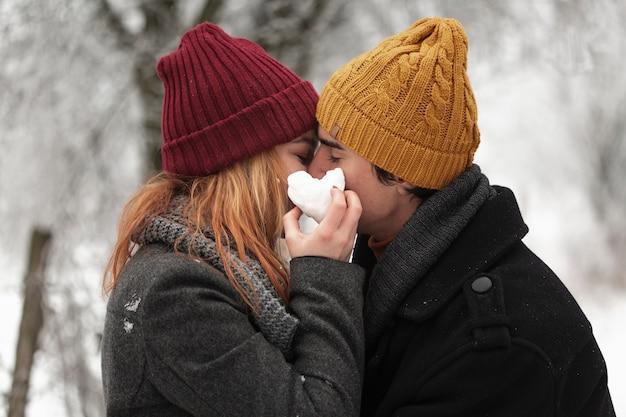Joven pareja besándose en la temporada de invierno tiro medio