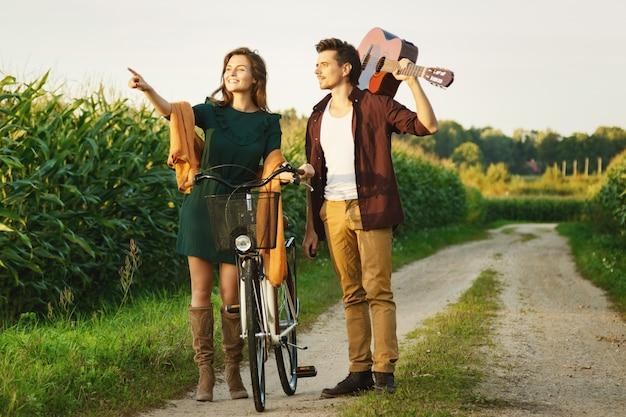 Joven pareja está caminando por camino rural