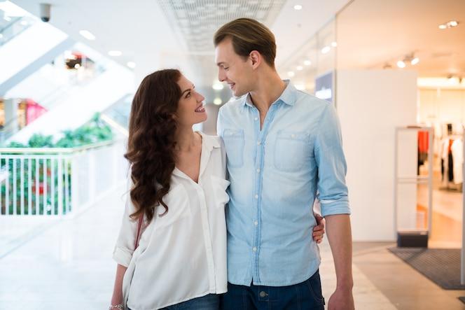 Joven pareja caminando en un centro comercial y divertirse