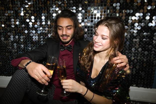 Joven pareja cariñosa tintineo con flautas de champán en la fiesta en el club nocturno por la pared brillante