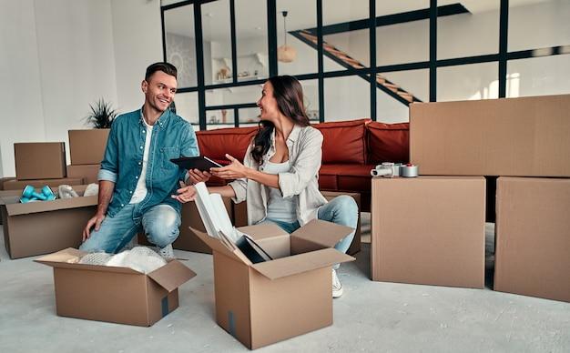 Una joven pareja casada desembalando cosas de cajas en el salón de la casa. feliz esposo y esposa se divierten, esperan un nuevo hogar. mudanza, compra de una casa, concepto de apartamento.