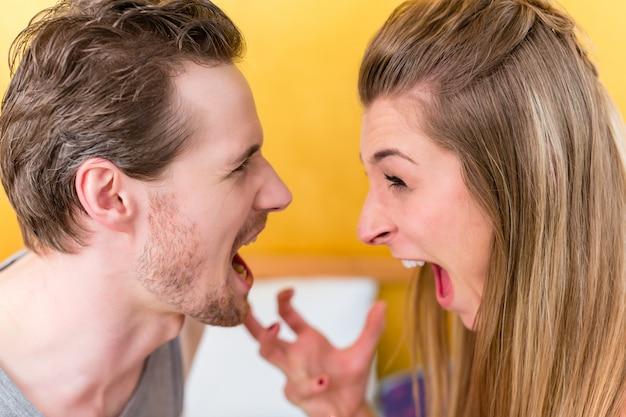 Joven pareja casada, mujer y hombre, en furiosa lucha mirando un