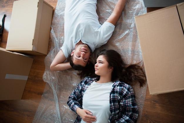 Una joven pareja casada en la sala de estar de la casa tumbada en el suelo cerca de cajas de cartón. hola, estamos contentos con el nuevo hogar. mudarse, comprar una casa, concepto de apartamento.