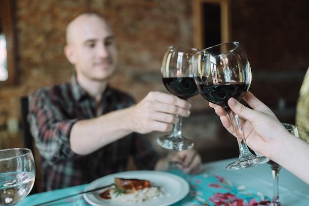 Joven pareja caucásica brindando por su cita en un restaurante