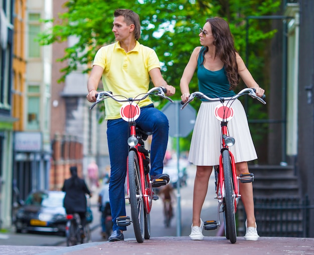 Joven pareja caucásica feliz en bicicleta en viejas calles de amsterdam