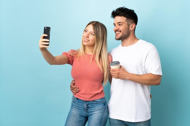 Joven pareja caucásica haciendo un selfie con el móvil