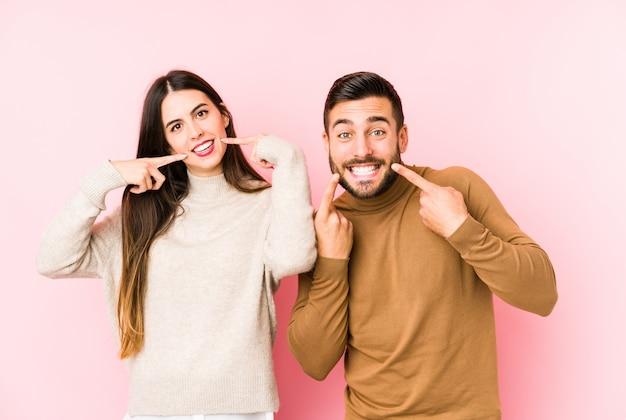 Joven pareja caucásica sonríe, señalando con el dedo en la boca.