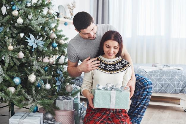 Joven pareja celebrando la navidad. un hombre de repente presentó un regalo a su esposa.