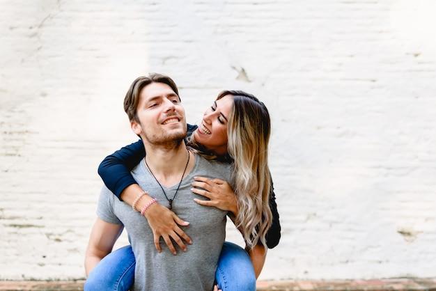 Joven pareja celebrando su amor con divertidos besos y caricias.