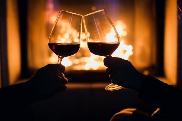 Joven pareja cena romántica con vino sobre fondo de chimenea