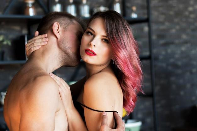 Una joven pareja y una chica con cabello rosado se abrazan apasionadamente
