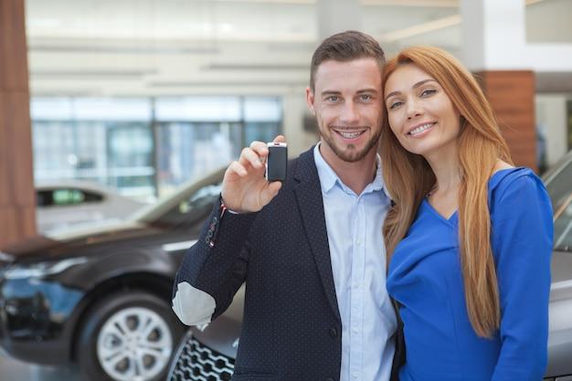 Joven pareja con clase comprando un coche de lujo en el concesionario