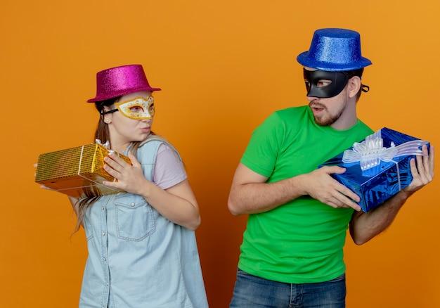 Joven pareja codiciosa con sombreros rosados y azules puestos en máscaras de ojos de mascarada sostiene cajas de regalo mirando el uno al otro aislado en la pared naranja