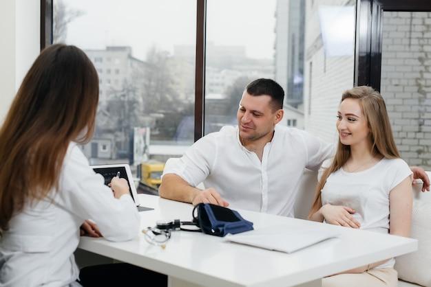 Una joven pareja en la consulta de un ginecólogo después de una ecografía. embarazo y cuidado de la salud.