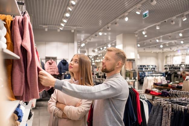 Joven pareja contemporánea de pie junto a la nueva colección de ropa casual en perchas mientras mira uno de ellos en el departamento de ropa