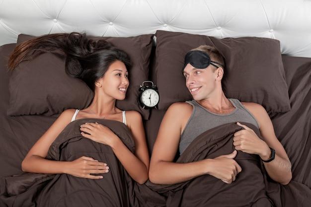 Una joven pareja contenta está acostada en la cama, con un despertador entre ellos.