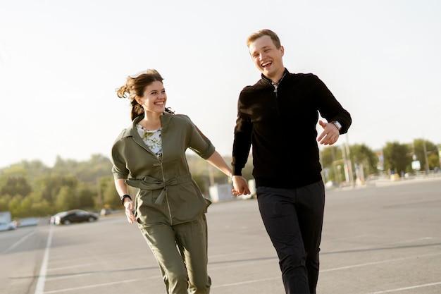 Una joven pareja corre en la calle el día de verano cogidos de la mano, vacaciones de fin de semana feliz vida