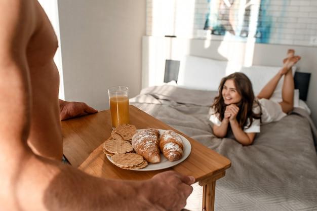 Joven pareja con delicioso desayuno en la cama. hermoso hombre sostiene la bandeja con cruasanes recién hechos, galletas y jugo