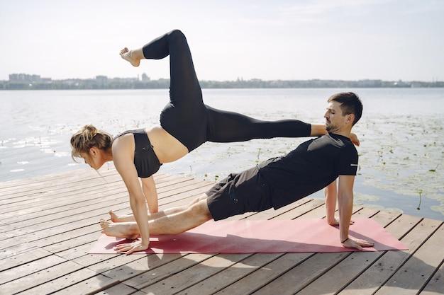Joven pareja deportiva haciendo yoga fitness. gente junto al agua.