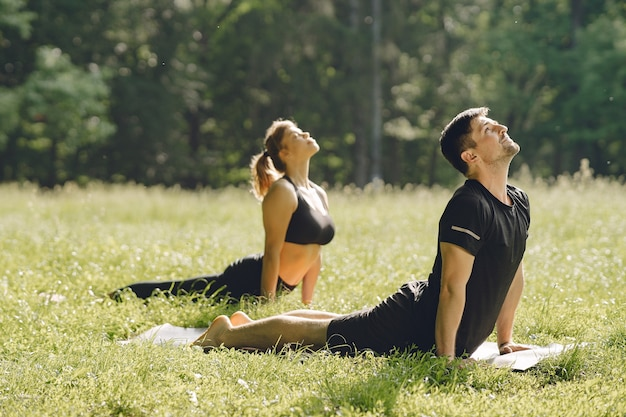 Joven pareja deportiva haciendo yoga fitness. personas en un parque de verano.