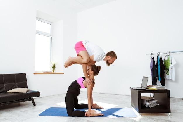 Joven pareja deportiva hermosa formación asanas de yoga en casa.