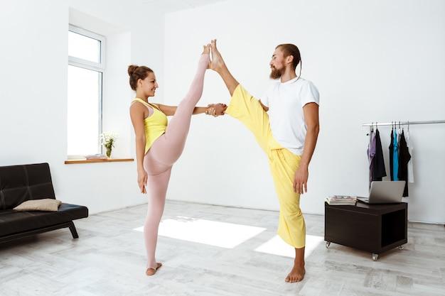 Joven pareja deportiva hermosa formación socio yoga asanas en casa.