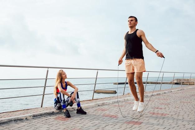 Joven pareja deportiva trabajando juntos en el muelle, cerca del mar.