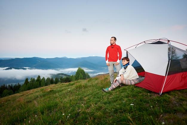 Joven pareja descansando cerca de camping en las montañas al amanecer.