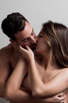 Joven pareja desnuda besándose