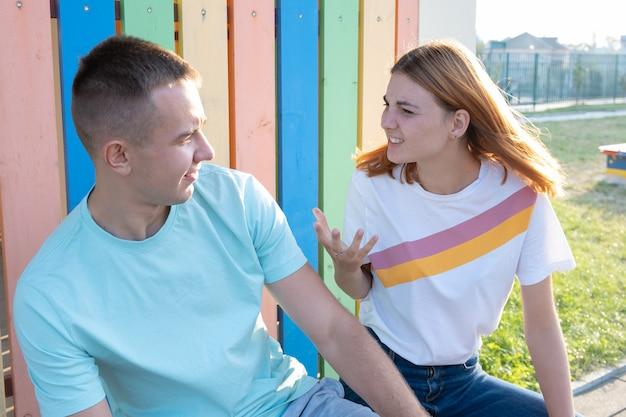 Joven pareja discutiendo al aire libre. chica pelirroja está enojada con su novio.