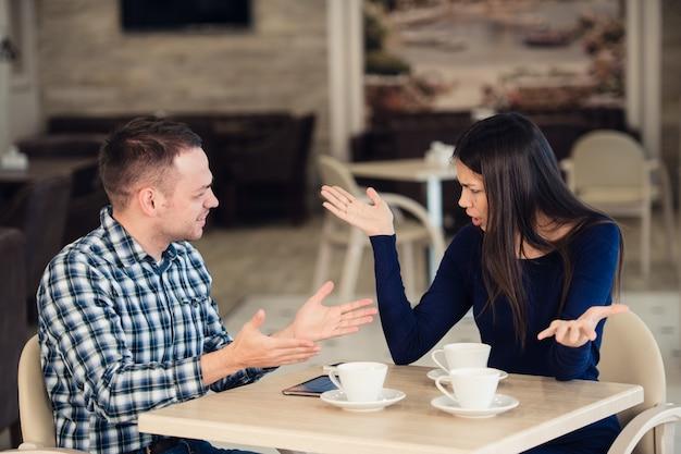 Joven pareja discutiendo en un café