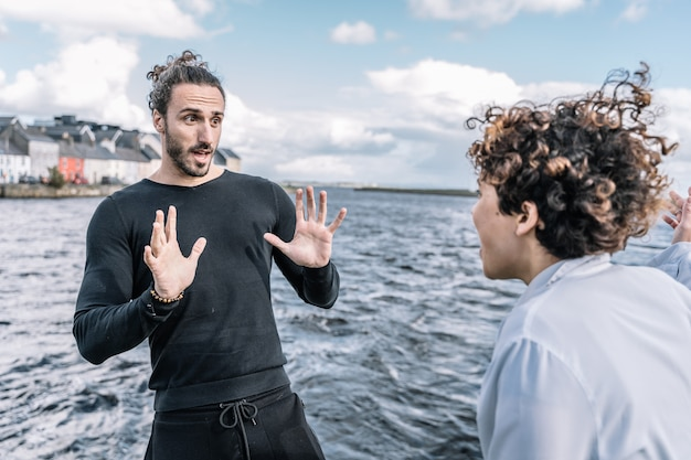 Joven pareja discutiendo expresivamente con el mar desenfocado