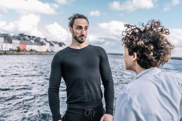 Joven pareja discutiendo con mar desenfocado