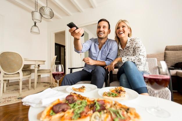 Joven pareja disfrutando de comer pizza y viendo la televisión en casa