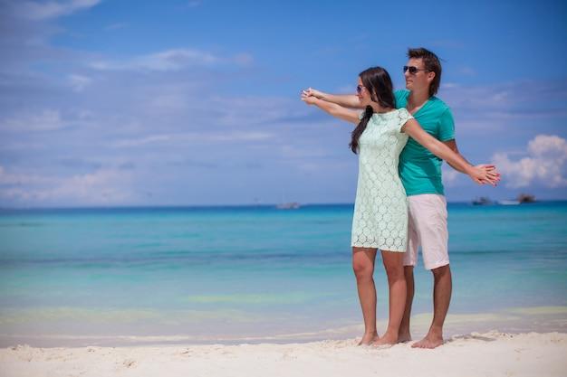 Joven pareja disfrutando mutuamente en la playa de arena blanca