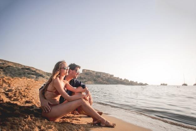 Joven pareja disfrutando de la vista del mar