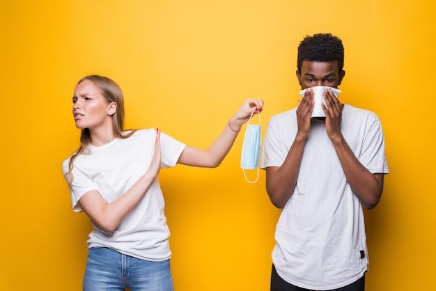 Joven pareja diversa, el hombre estornuda a las mujeres conmocionadas aisladas en el estudio de pared amarilla