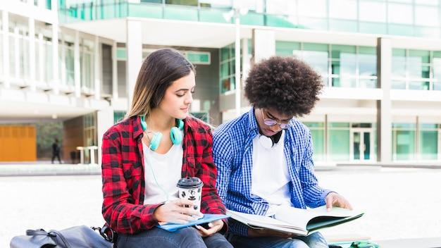 Joven pareja diversa sentada fuera del edificio de la universidad