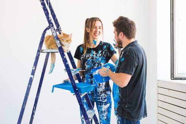 Joven pareja divertida con gato haciendo renovación