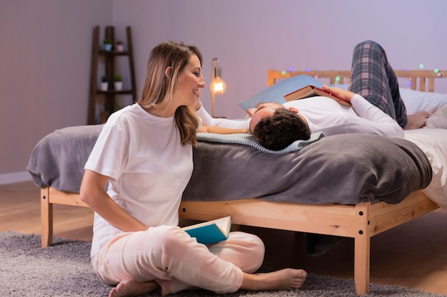 Joven pareja se divierte en la cama